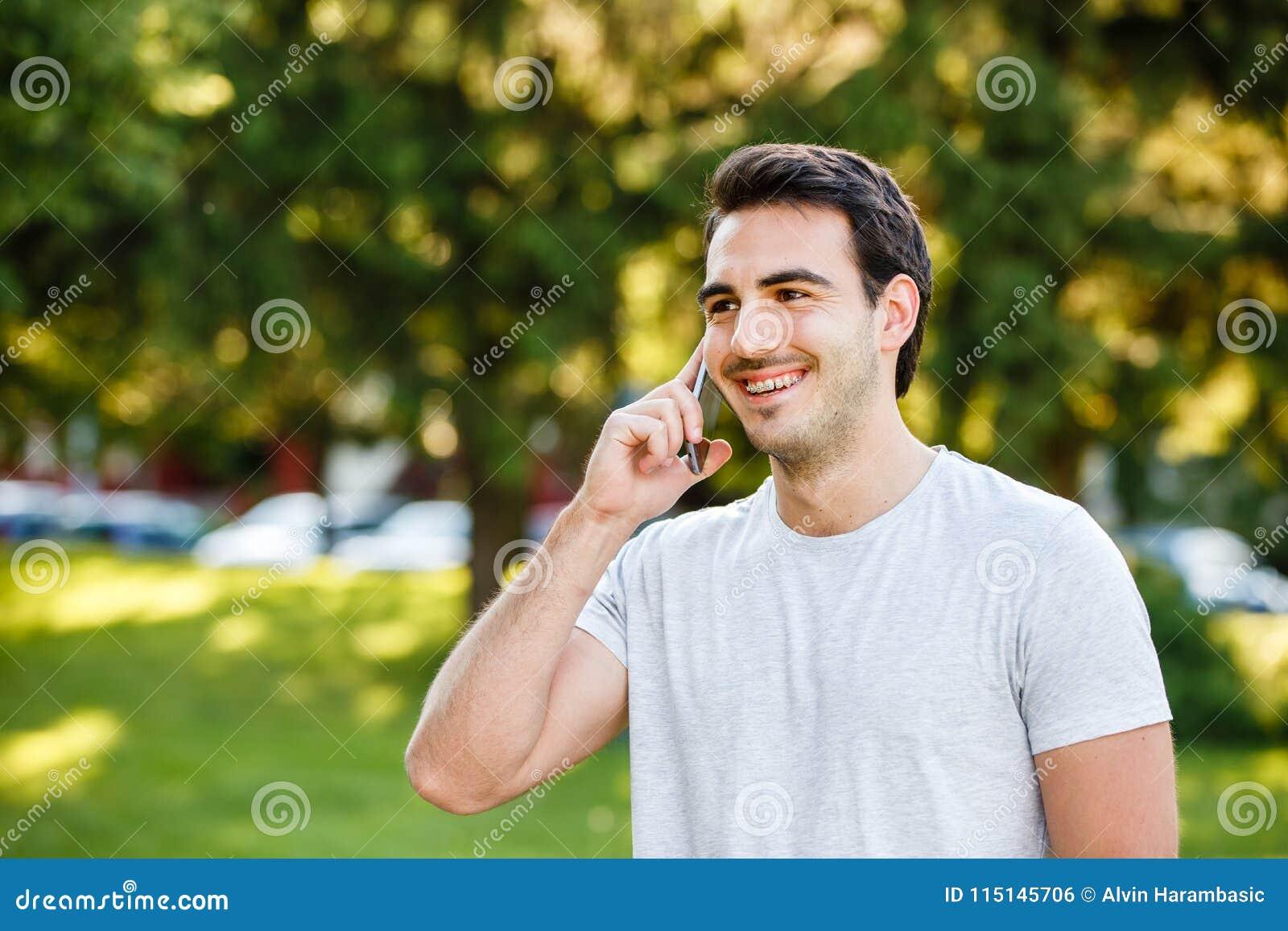 Przystojny młody człowiek w parkowym talkig na jego telefonie
