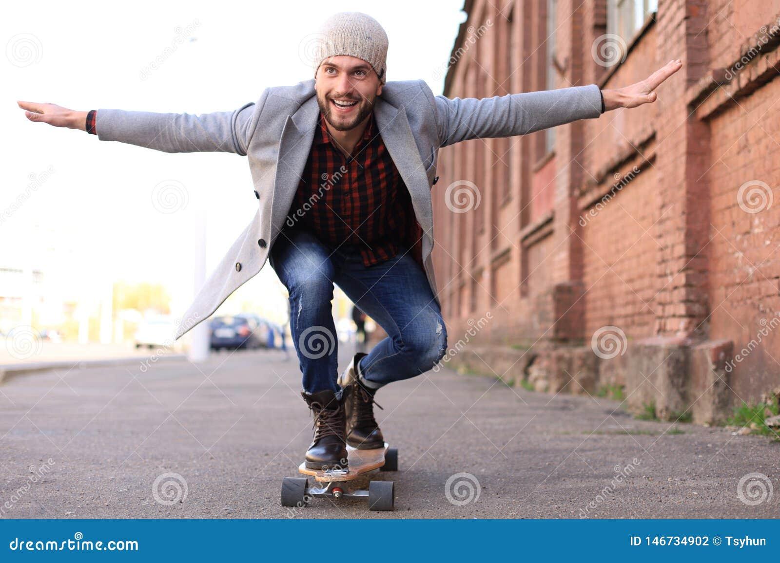 Przystojny młody człowiek w popielatym żakiecie i kapeluszu na longboard na ulicie w mieście Miastowy je?dzi? na deskorolce poj?c