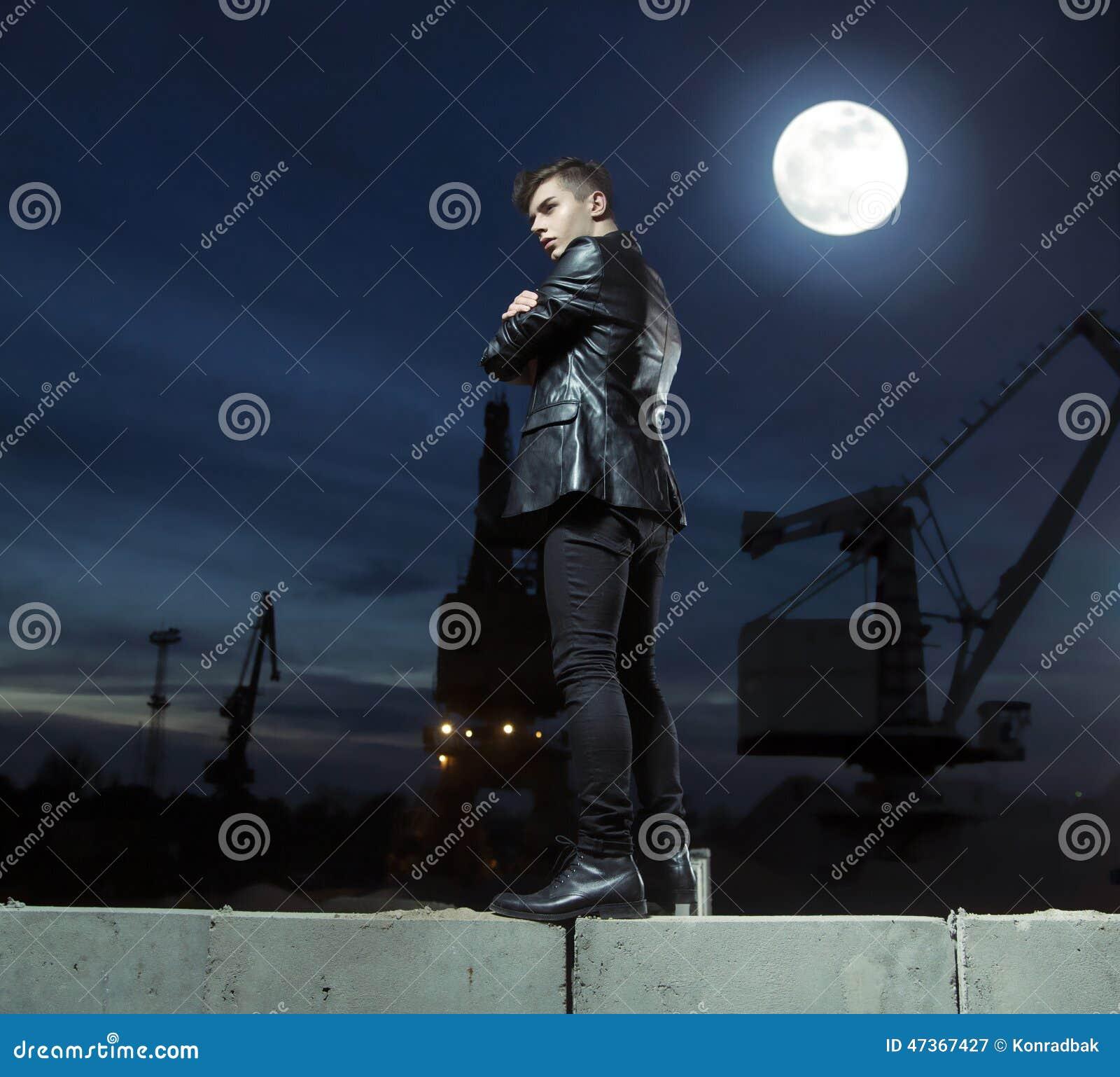 Przystojny młody facet nad budynku tłem