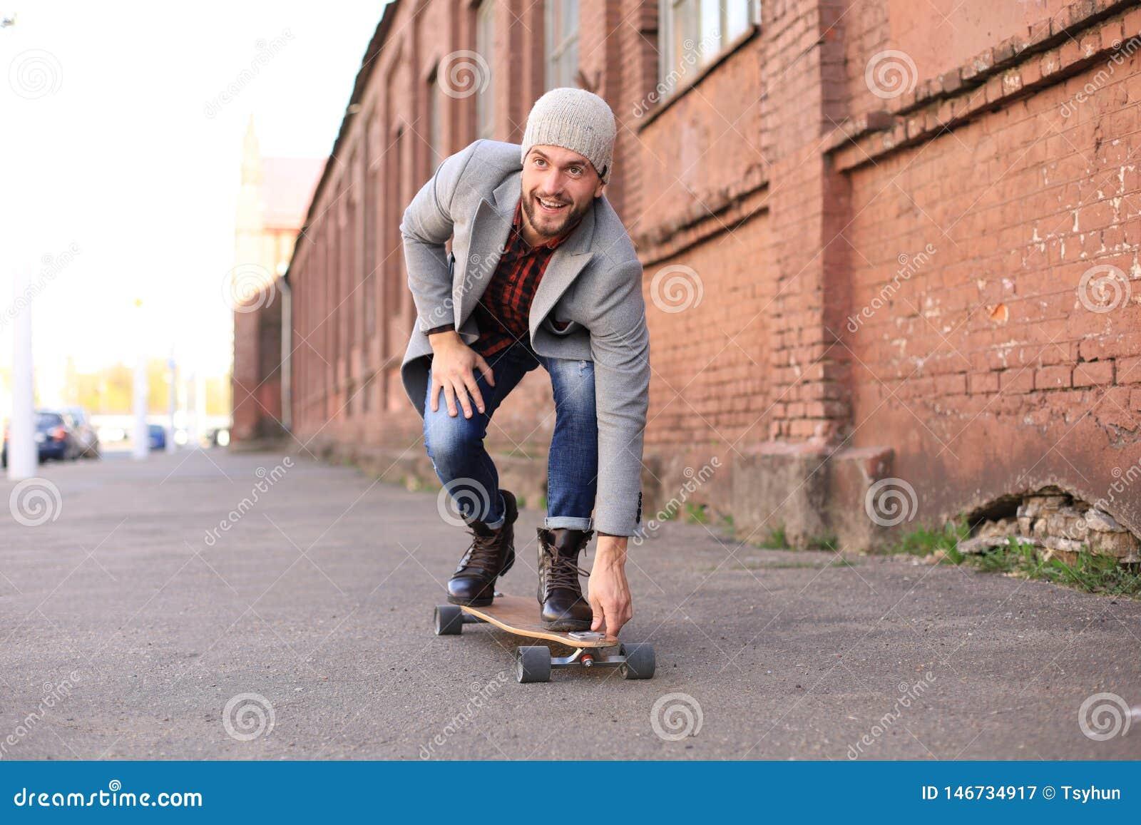 Przystojny m?ody cz?owiek w popielatym ?akiecie i kapeluszu na longboard na ulicie w mie?cie Miastowy je?dzi? na deskorolce poj?c