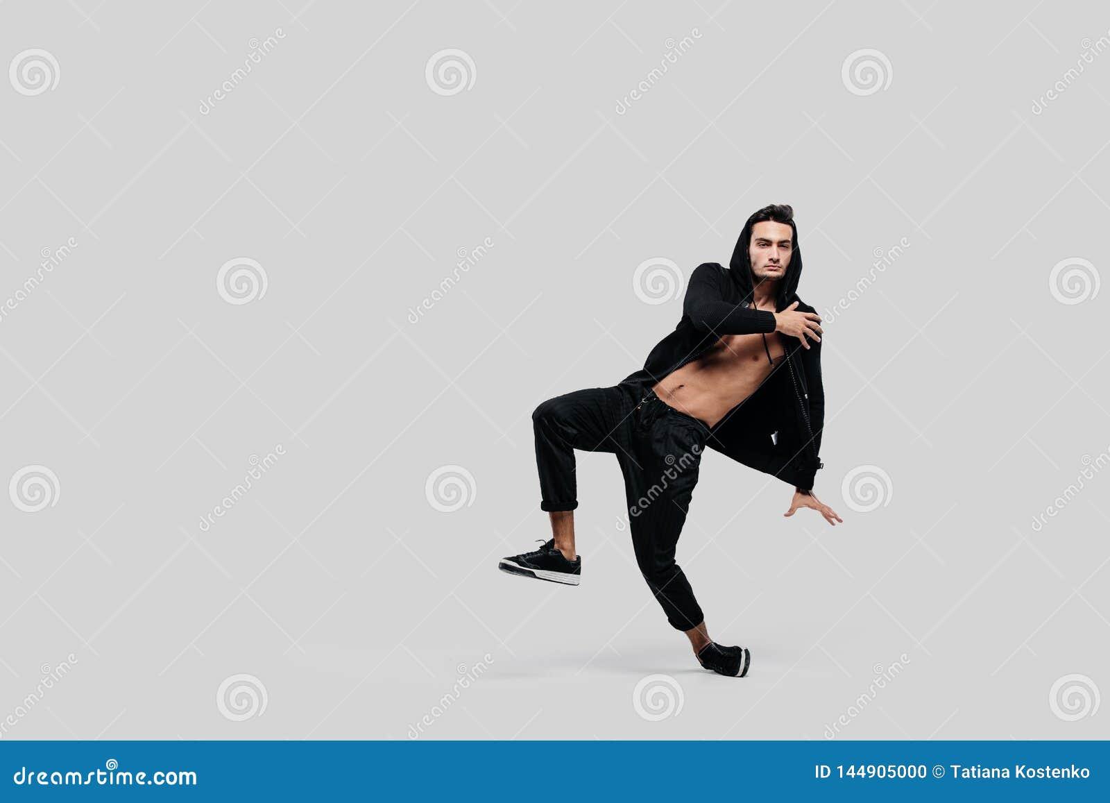 Przystojny m?ody tancerz uliczny taniec ubiera? w czarnych spodniach, bluzie sportowej na nagiej p??postaci i kapiszonu tanach na