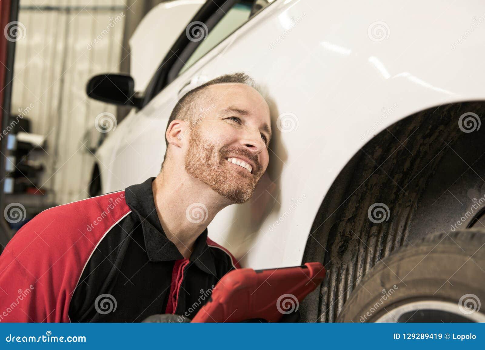 Przystojny mechanik opierający się na samochodzie w auto remontowym sklepie z pastylką na ręce