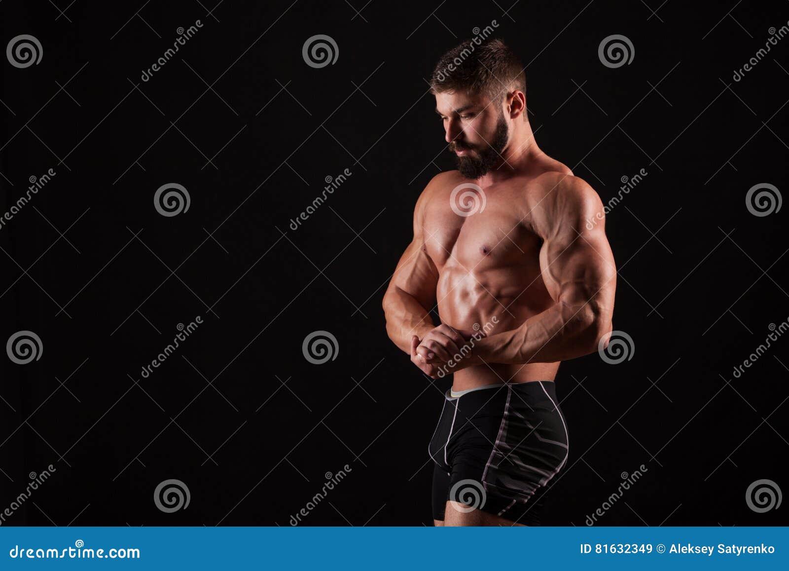 Przystojny mięśniowy bodybuilder pozuje nad czarnym tłem