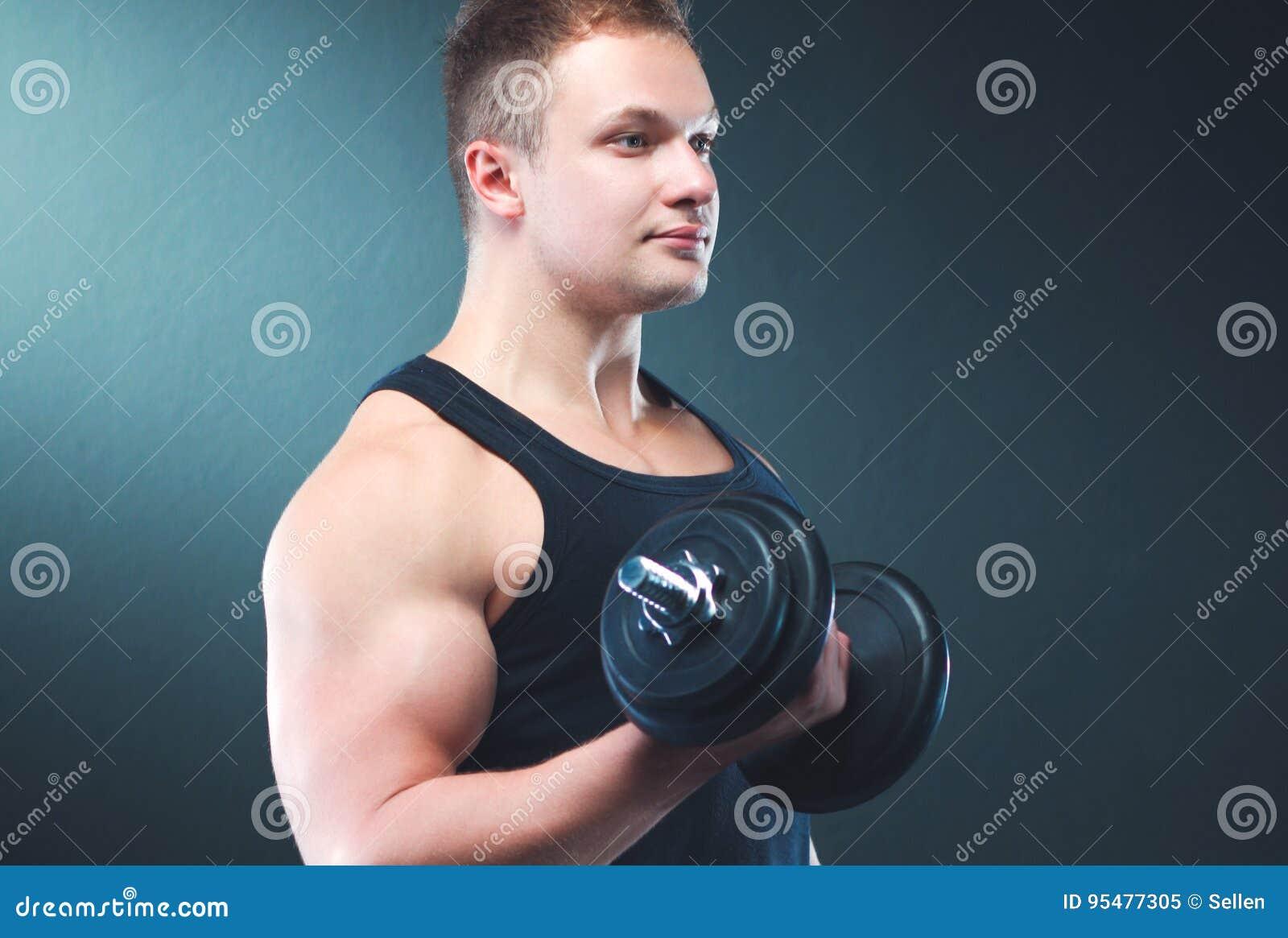 Przystojny mięśniowy mężczyzna pracujący z dumbbells out