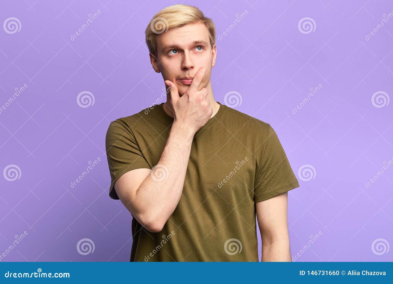 Przystojny poważny młody człowiek przyglądający w górę rozważnego spojrzenia z