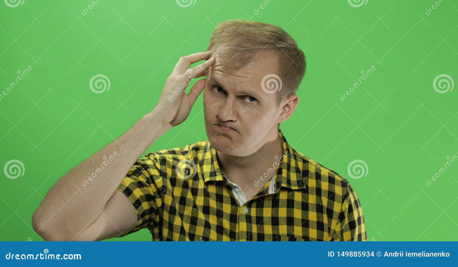 Przystojny rozważny mężczyzna w żółty koszulowy patrzeć w kamerze i myśleć