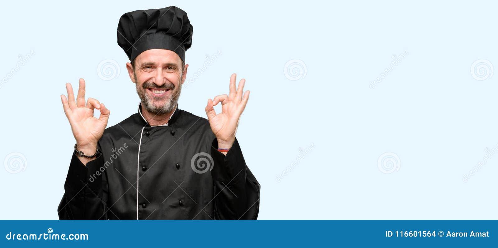 Przystojny seniora kucharza mężczyzna odizolowywający nad błękitnym tłem
