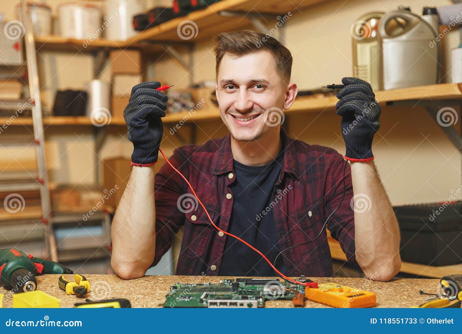 Przystojny uśmiechnięty młody człowiek pracuje w ciesielka warsztacie przy drewnianym stołowym miejscem z kawałkiem drewno