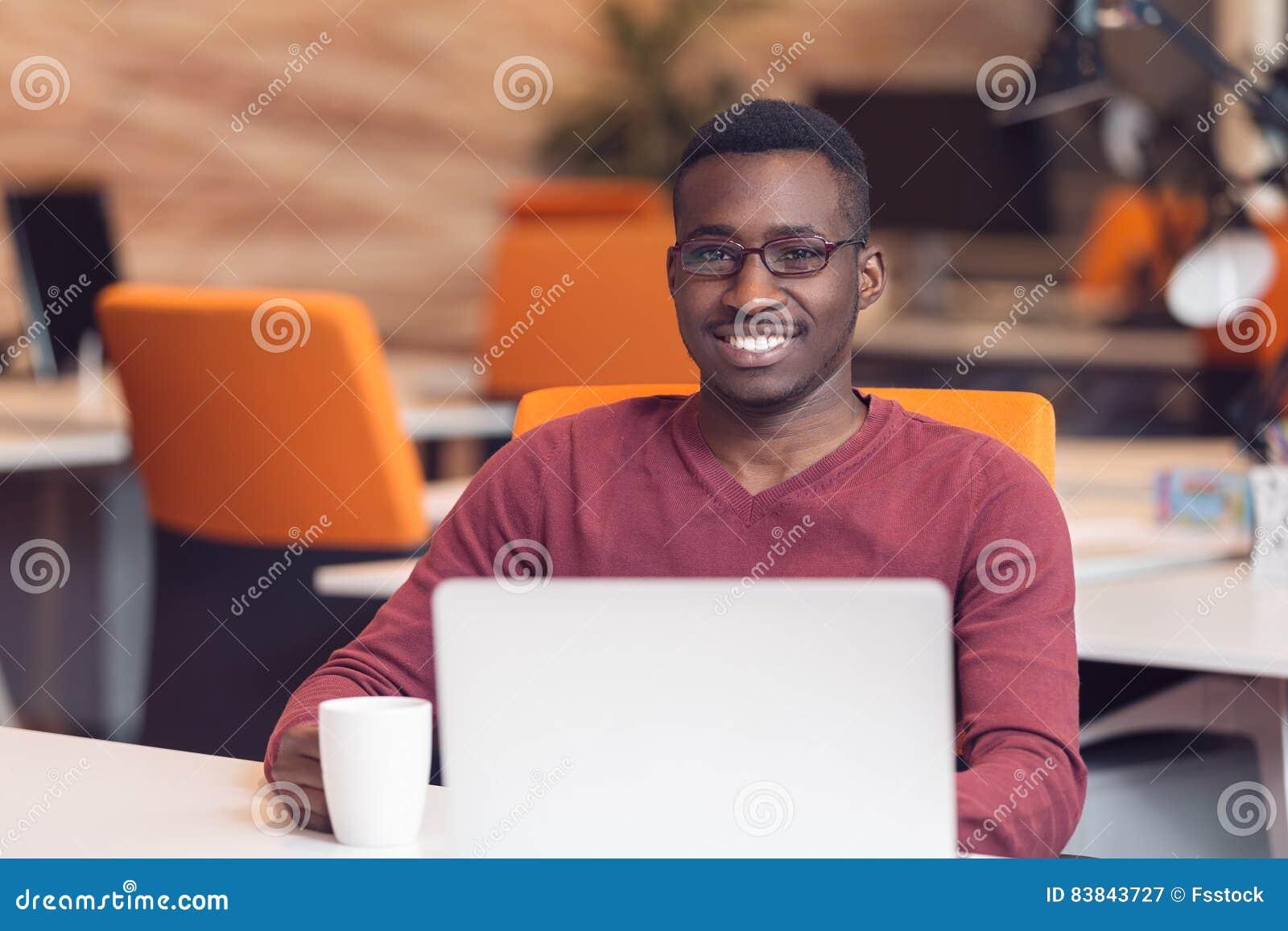 Przystojny uśmiechnięty pomyślny amerykanina afrykańskiego pochodzenia mężczyzna używa laptop