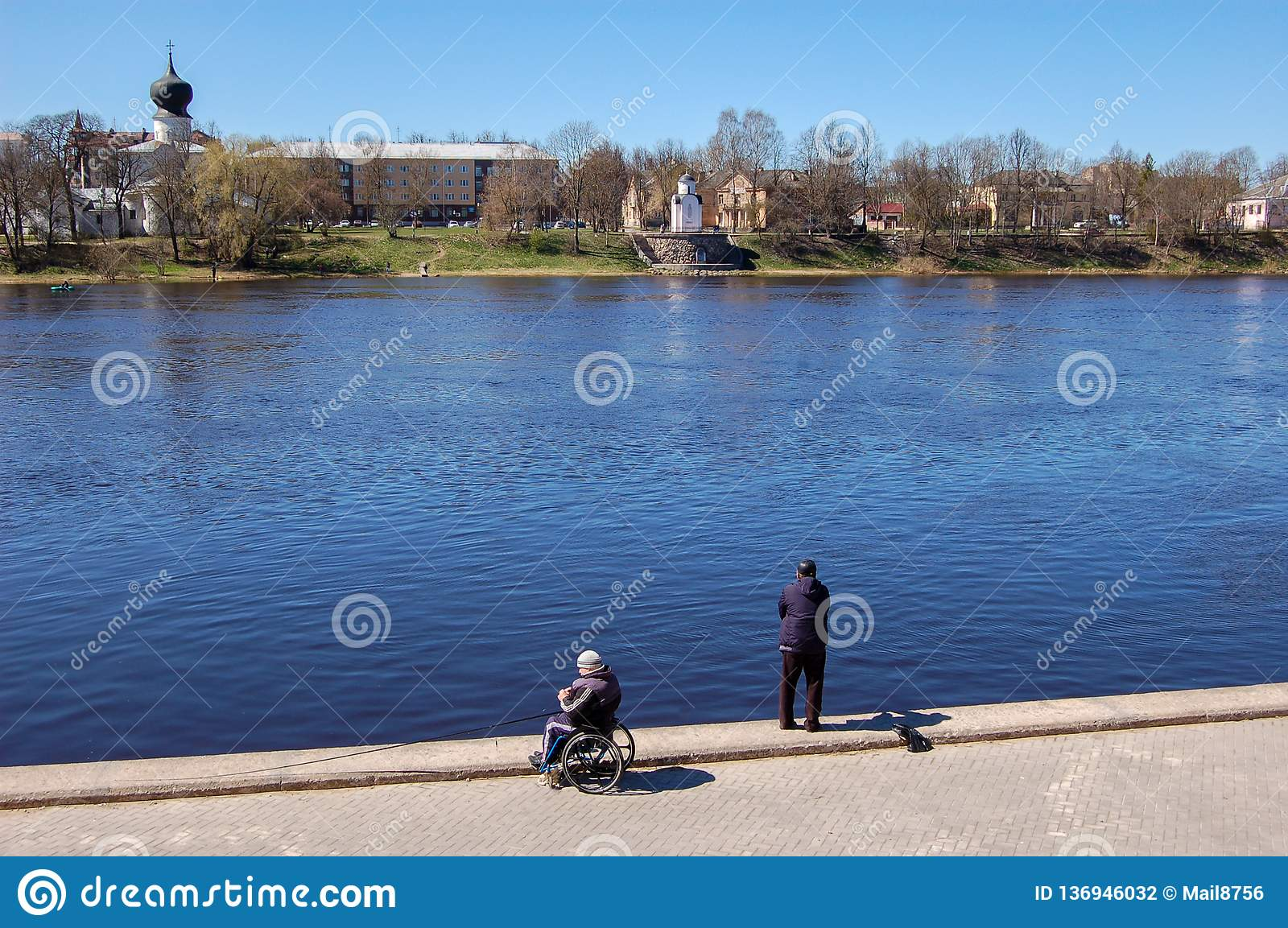 Pskov, Russia 04 may 2017. A man in a wheelchair fishing. Numerous fishermen on the Velikaya river near the Kremlin