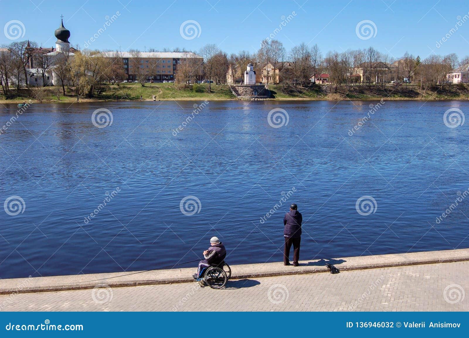 Pskov, Russland 04 kann 2017 Ein Mann in einem Rollstuhlfischen Zahlreiche Fischer auf dem Velikaya-Fluss nahe dem Kreml