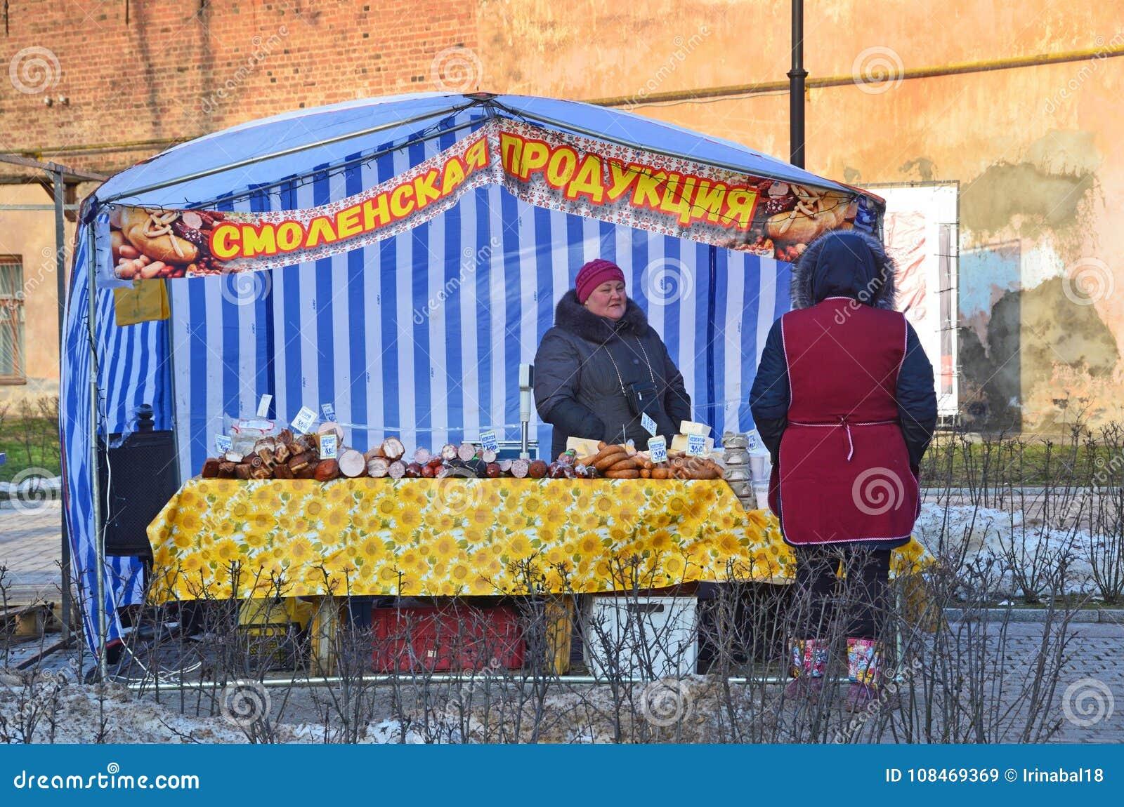 Pskov Ryssland, December, 31, 2017 Kvinna på helgmarknad på den Pushkin gatan i Pskov ` För paviljong`-Smolensk produkter,