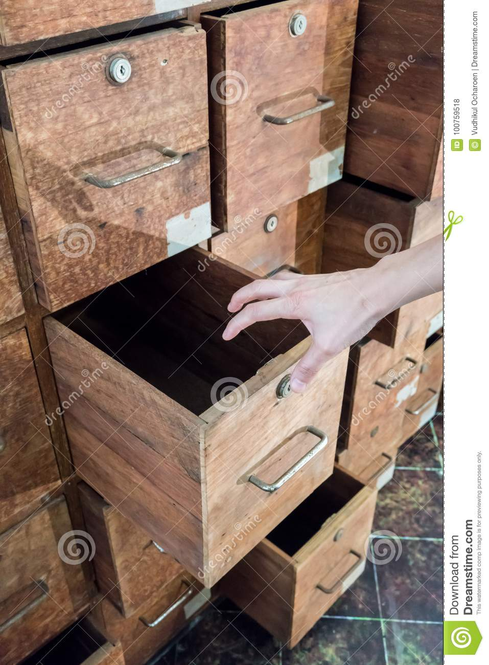 Psychiatric hand opening a drawer of old haunted wooden cabinet