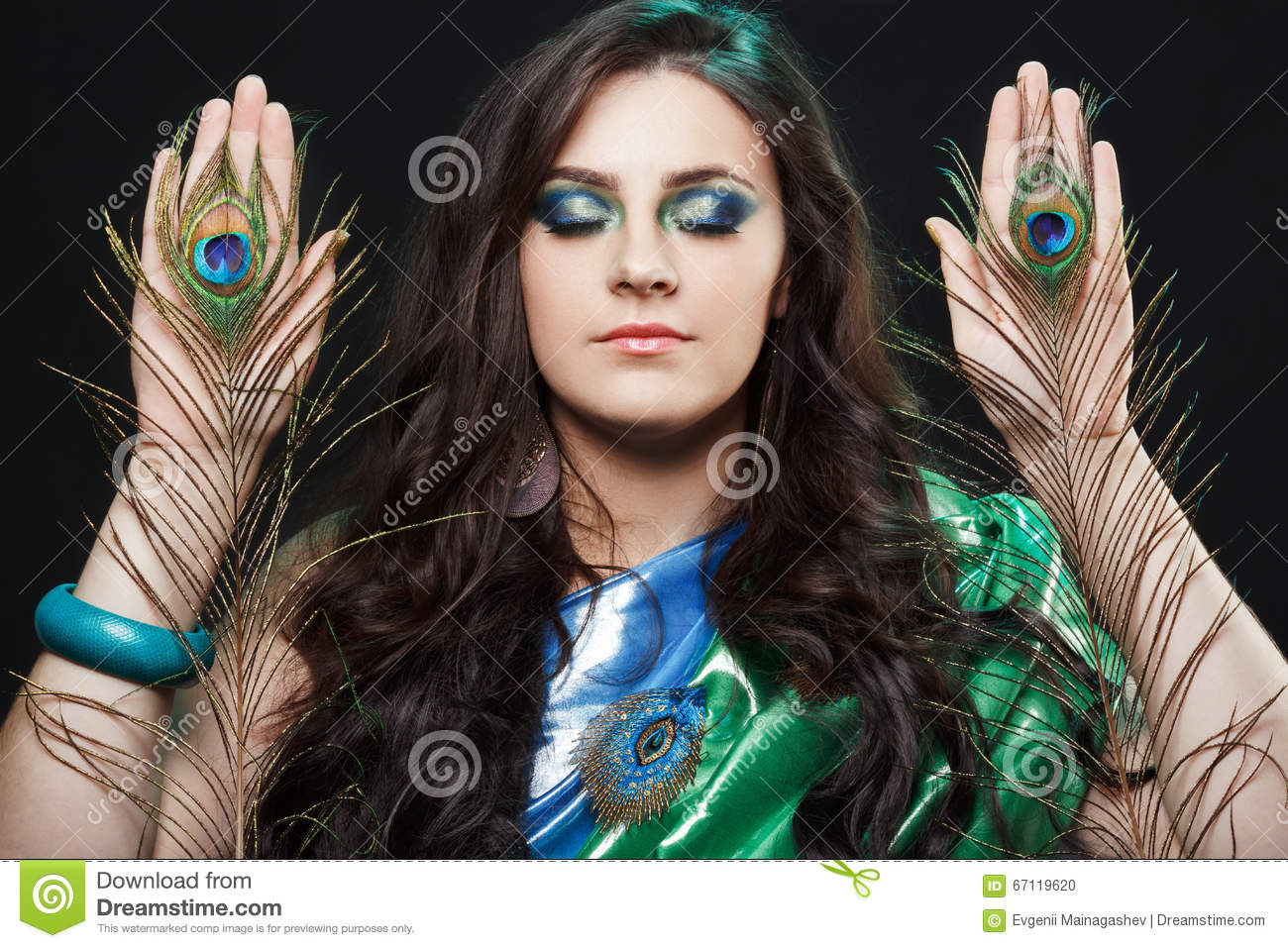Psychic abilities psychics communicate with spirits. Beauty portrait of girl holding peacock feathers, bright clothes