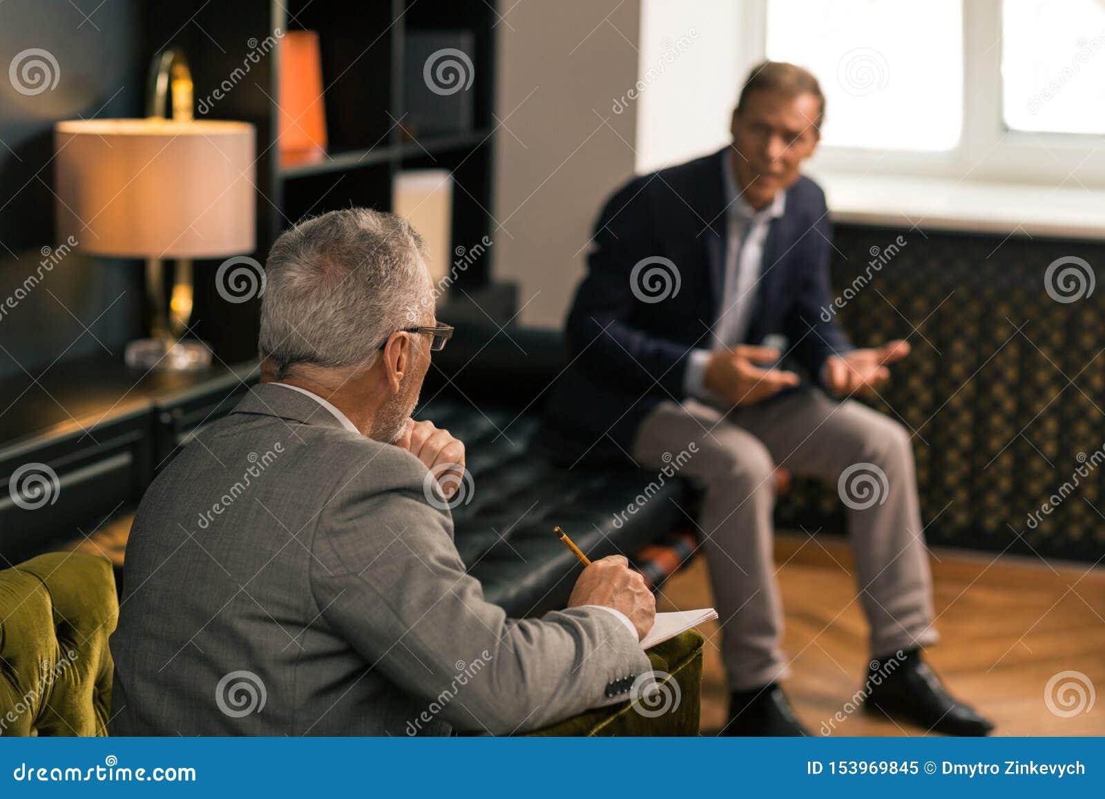 Psychothérapeute faisant des notes et écoutant un patient