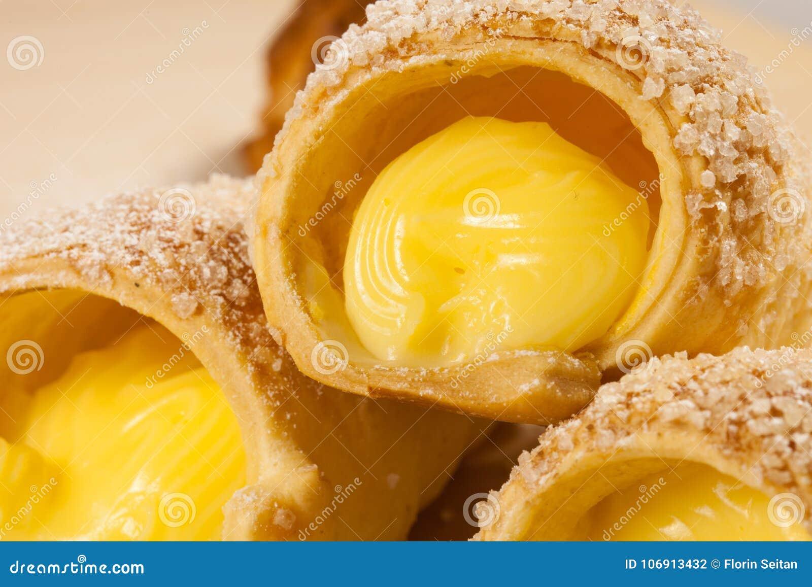 Ptysiowego ciasta wanilia uzbrajać w rogi na drewnianej desce
