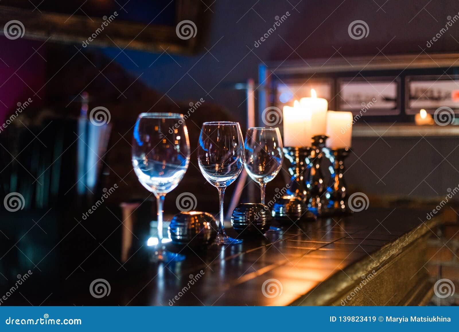 Puści win szkła, świeczki z iluminacji świateł tłem i