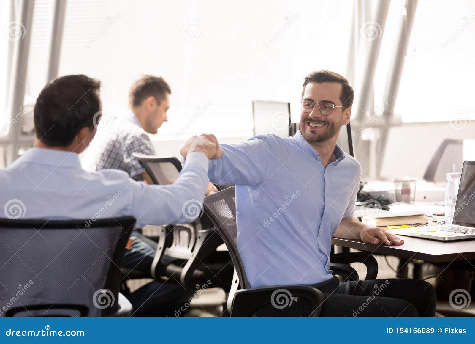 Puño masculino de los colegas que topa en el lugar de trabajo, celebrando éxito del trabajo en equipo