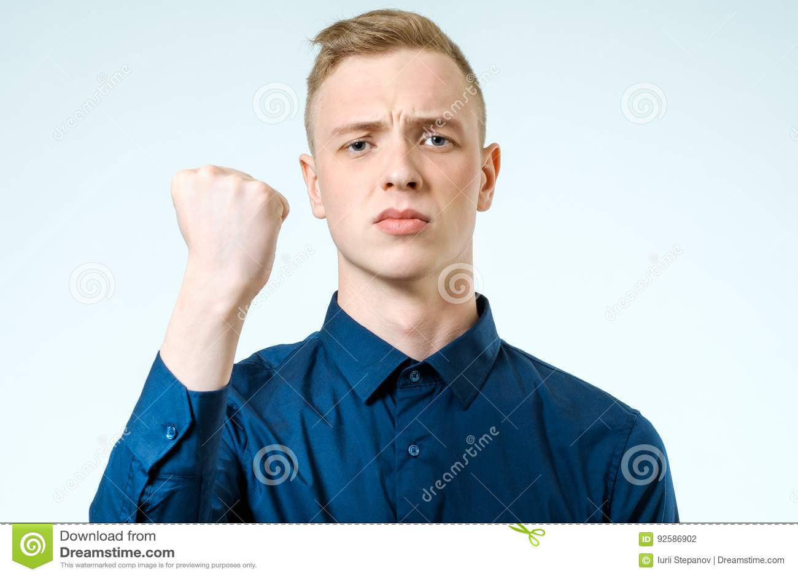 Puño que gesticula enojado del hombre joven levantado