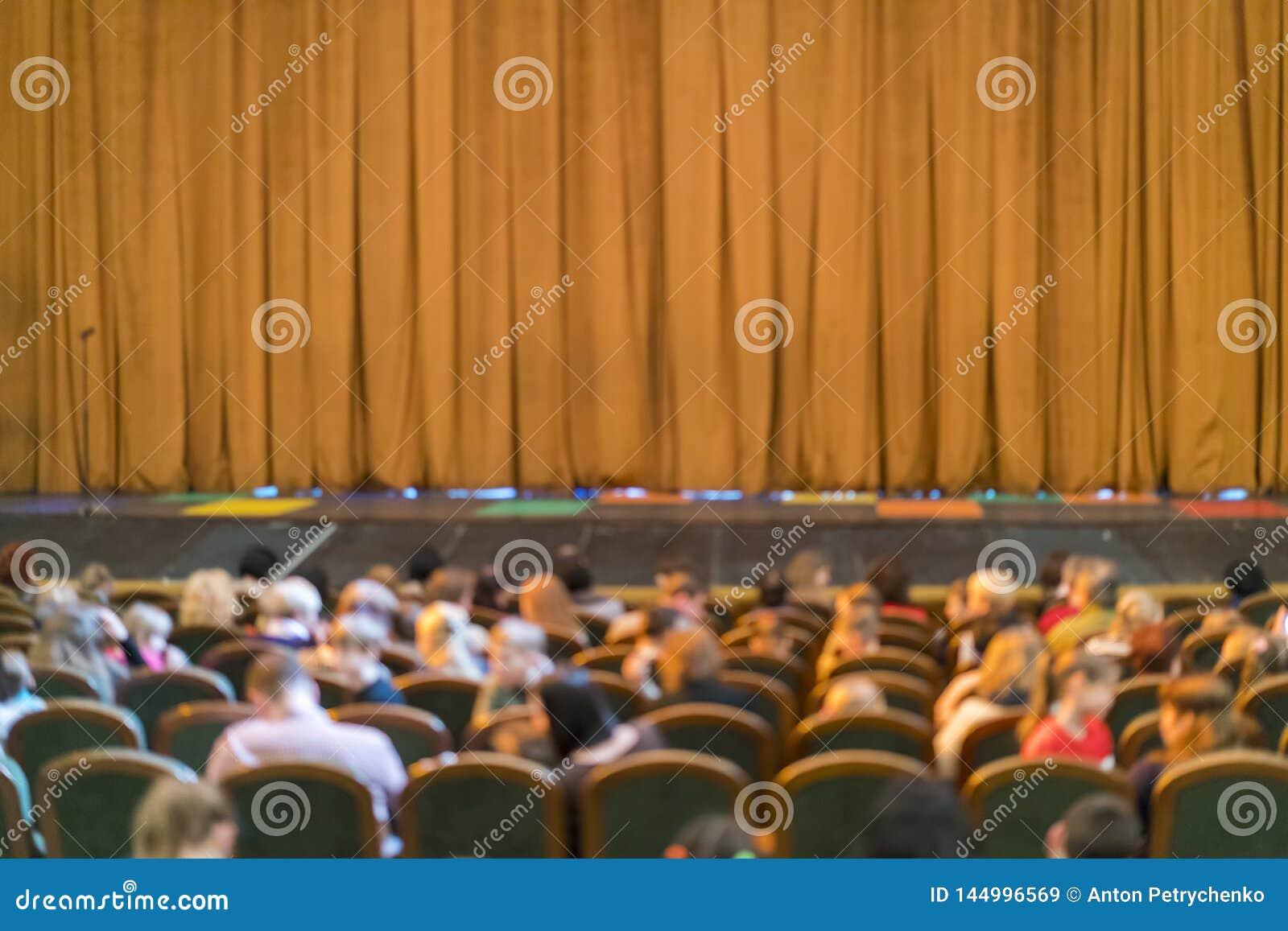 Publiek in Theater gesloten stadiumgordijn in een theater onscherp