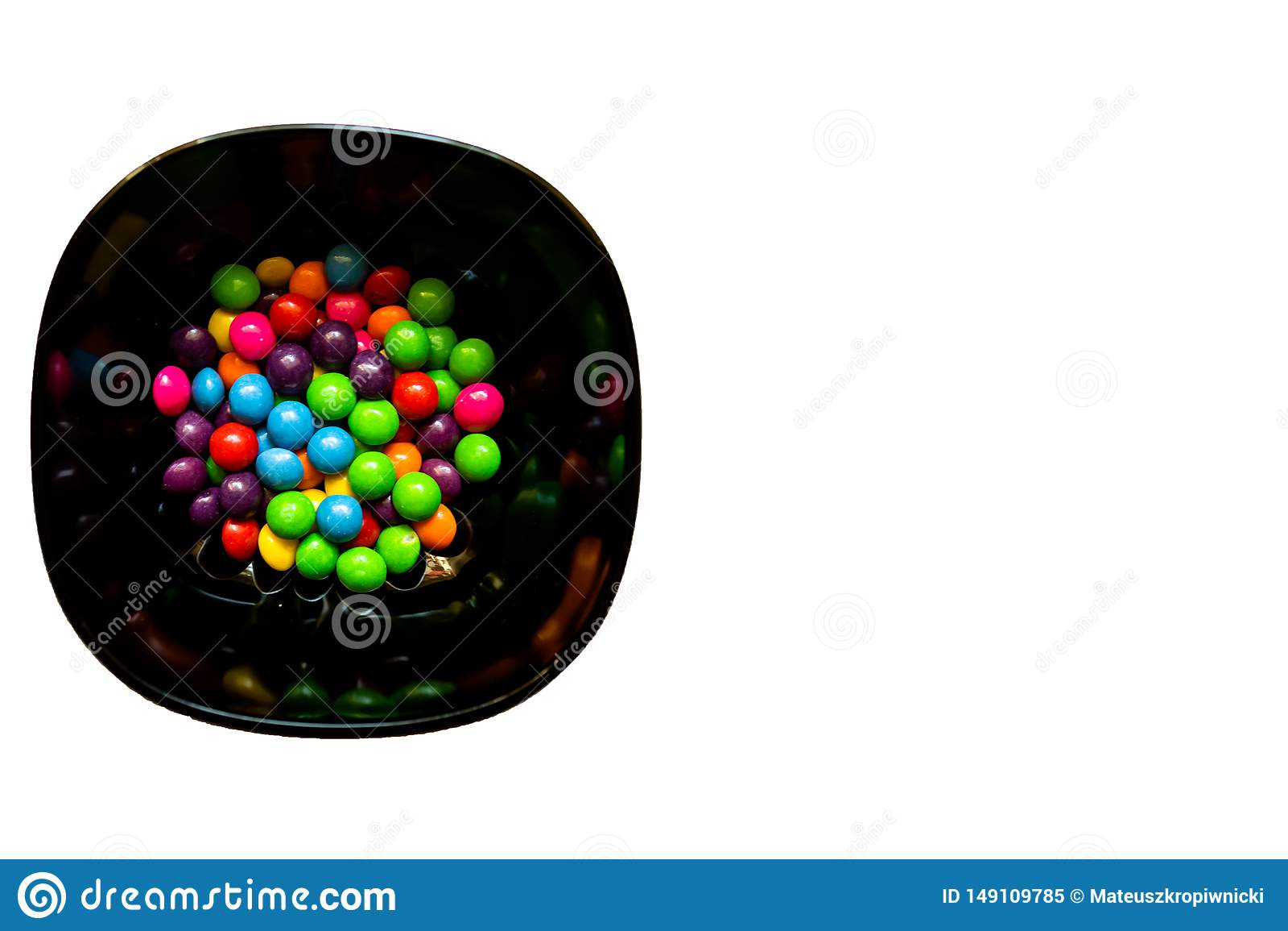 Puchar kolorowi cukierki na białym tle z kopii przestrzenią