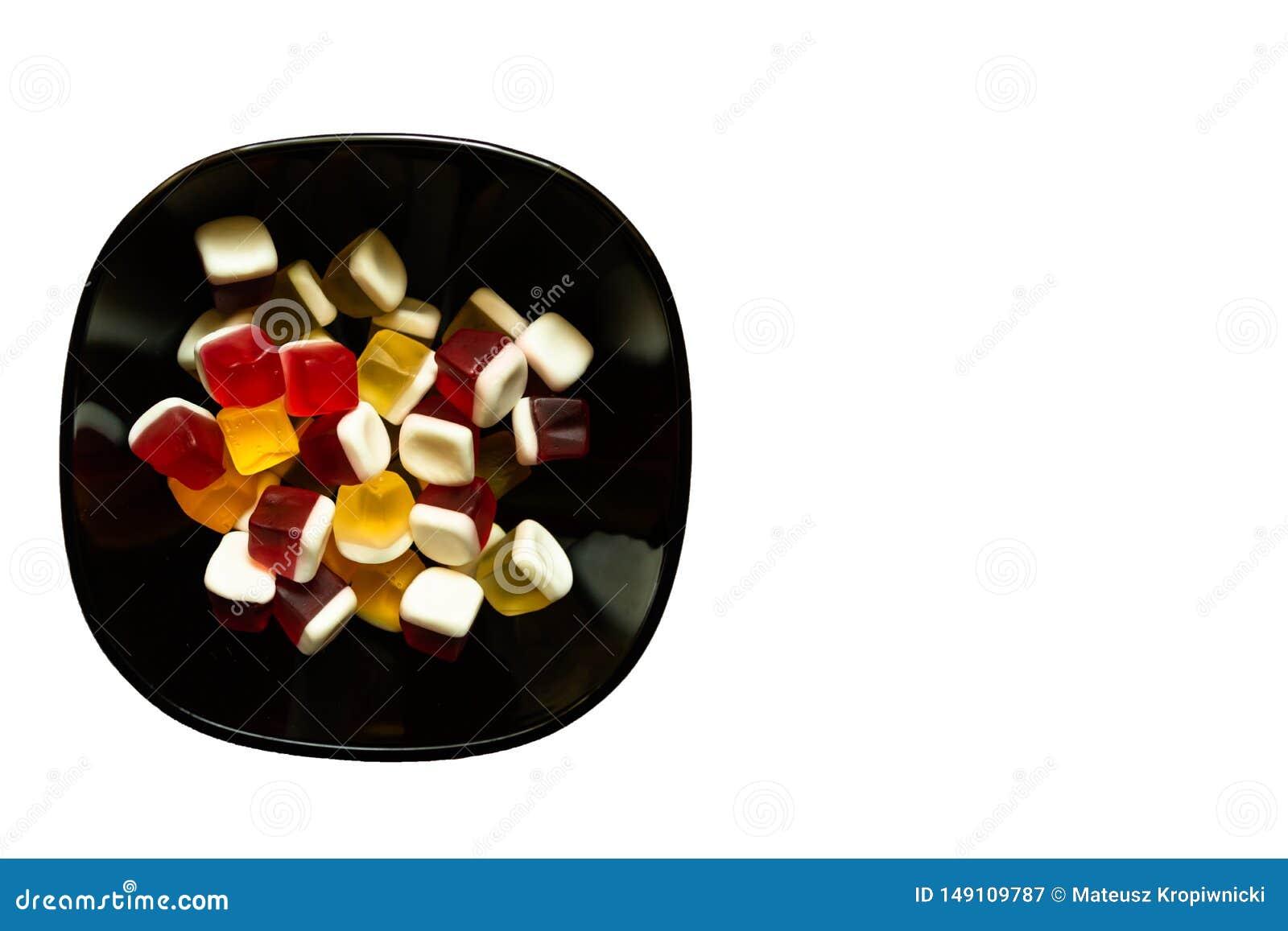 Puchar kolorowy sześcian kształtujący galaretowi cukierki na białym tle z kopii przestrzenią