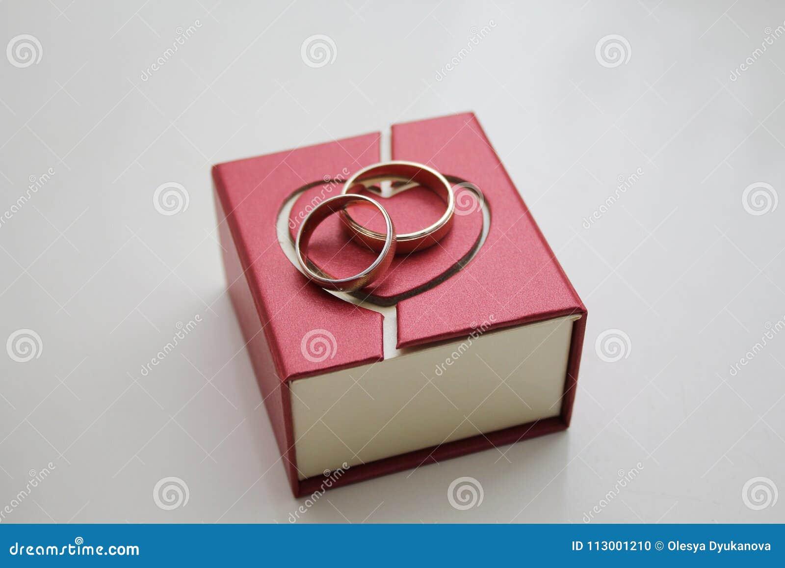 Pudełko z obrączkami ślubnymi na białym tle