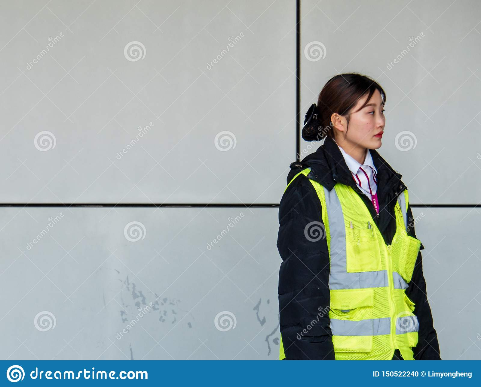 PUDONG SHANGHAI - 13 MARS 2019 - kvinnlig flygplatsanställd på den Pudong flygplatsen, Shanghai med kopieringsutrymme