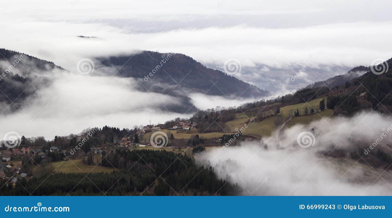Pueblo alpino en la niebla Francia, rhone-Alpes