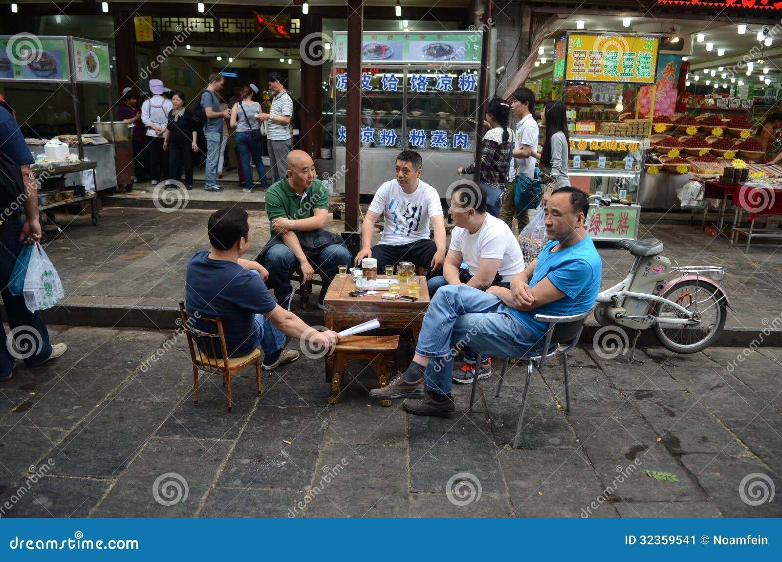 Pueblo chino local que bebe afuera