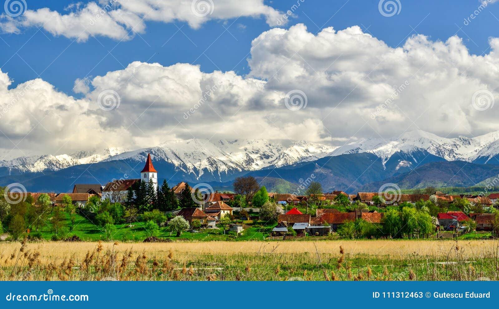 Pueblo de Transilvania en Rumania, en la primavera con las montañas en el fondo