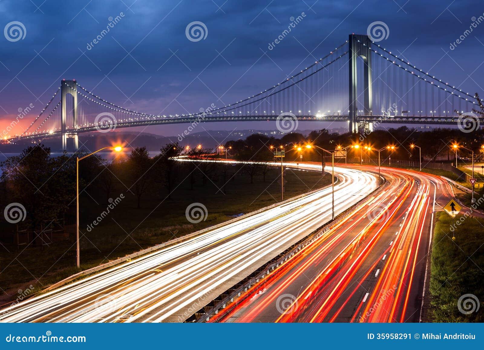 Puente de los estrechos de Verrazano sobre los rastros ligeros del tráfico de la ruta verde de la correa.