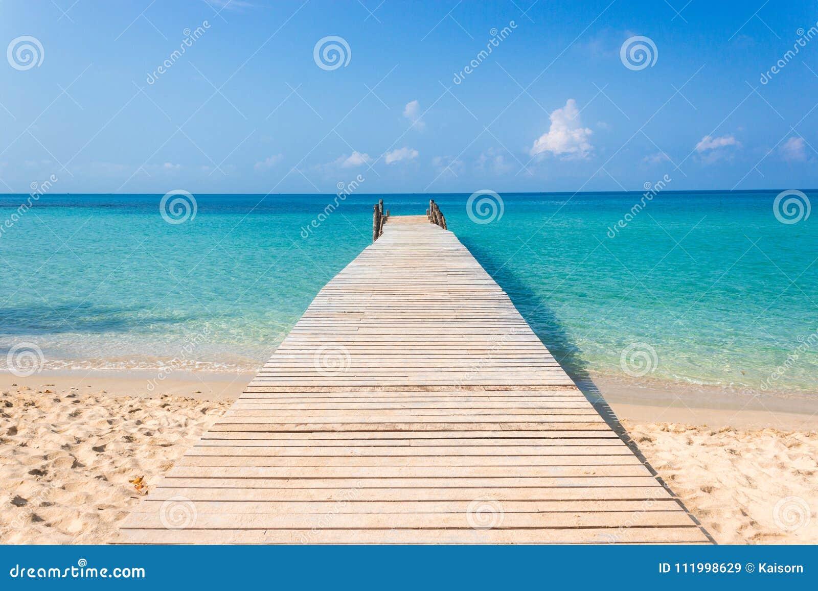 Puente de madera en la playa tropical y el cielo azul