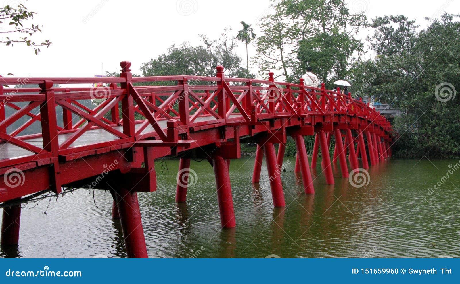 Puente de madera rojo por el lago azul