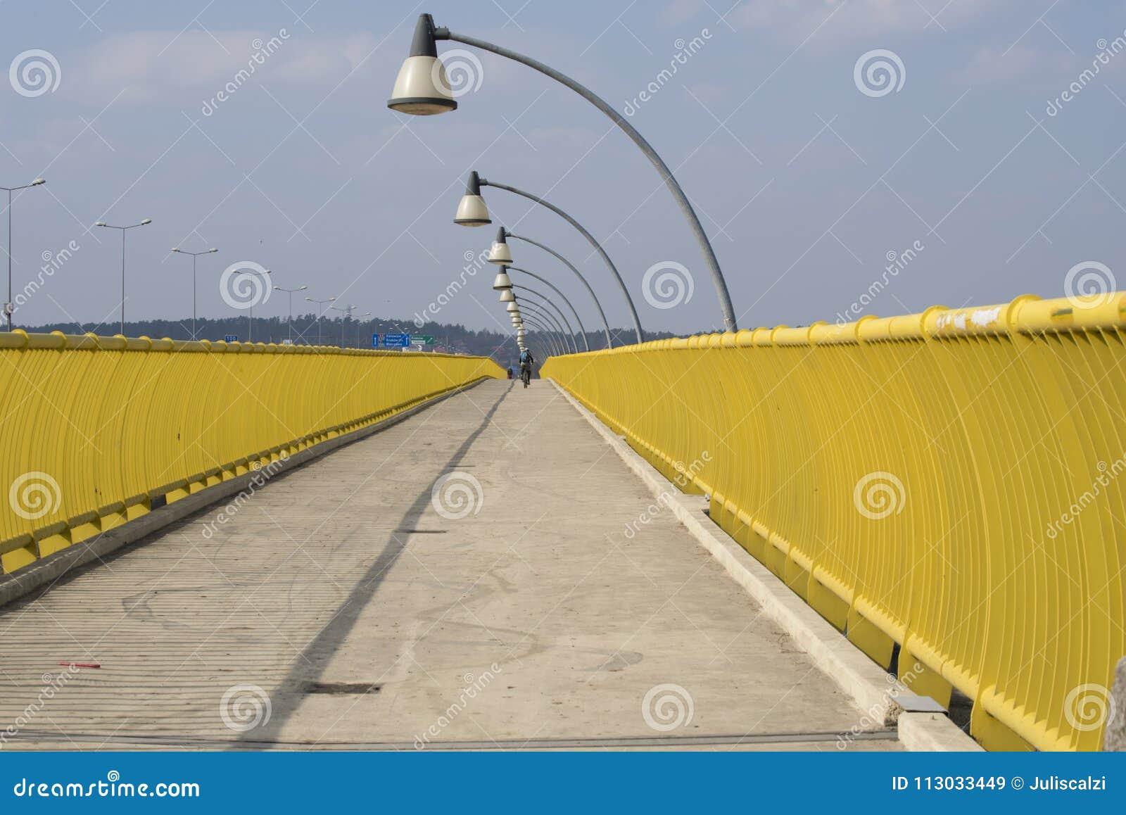 Puente de travesía pedistrian amarillo sobre el río Vistula en Kraków,