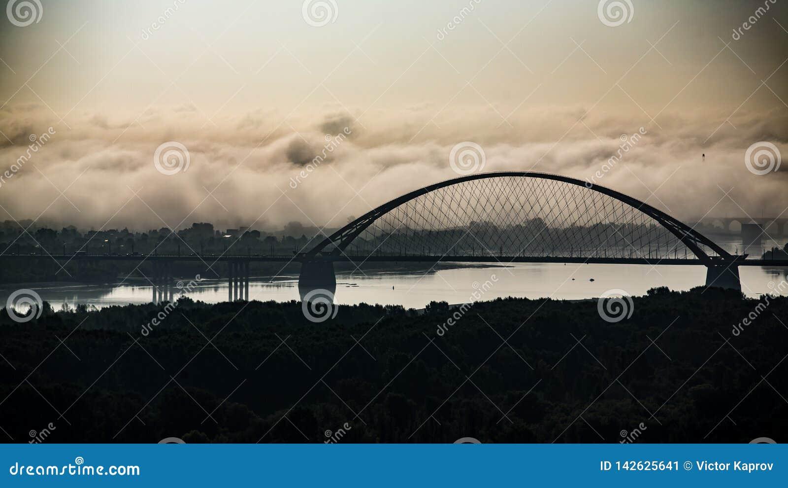 Puente en la niebla en la salida del sol