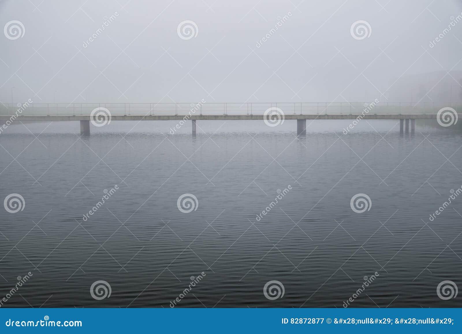 Puente en tiempo brumoso pacífico tranquilo en el paisaje soñador blanco