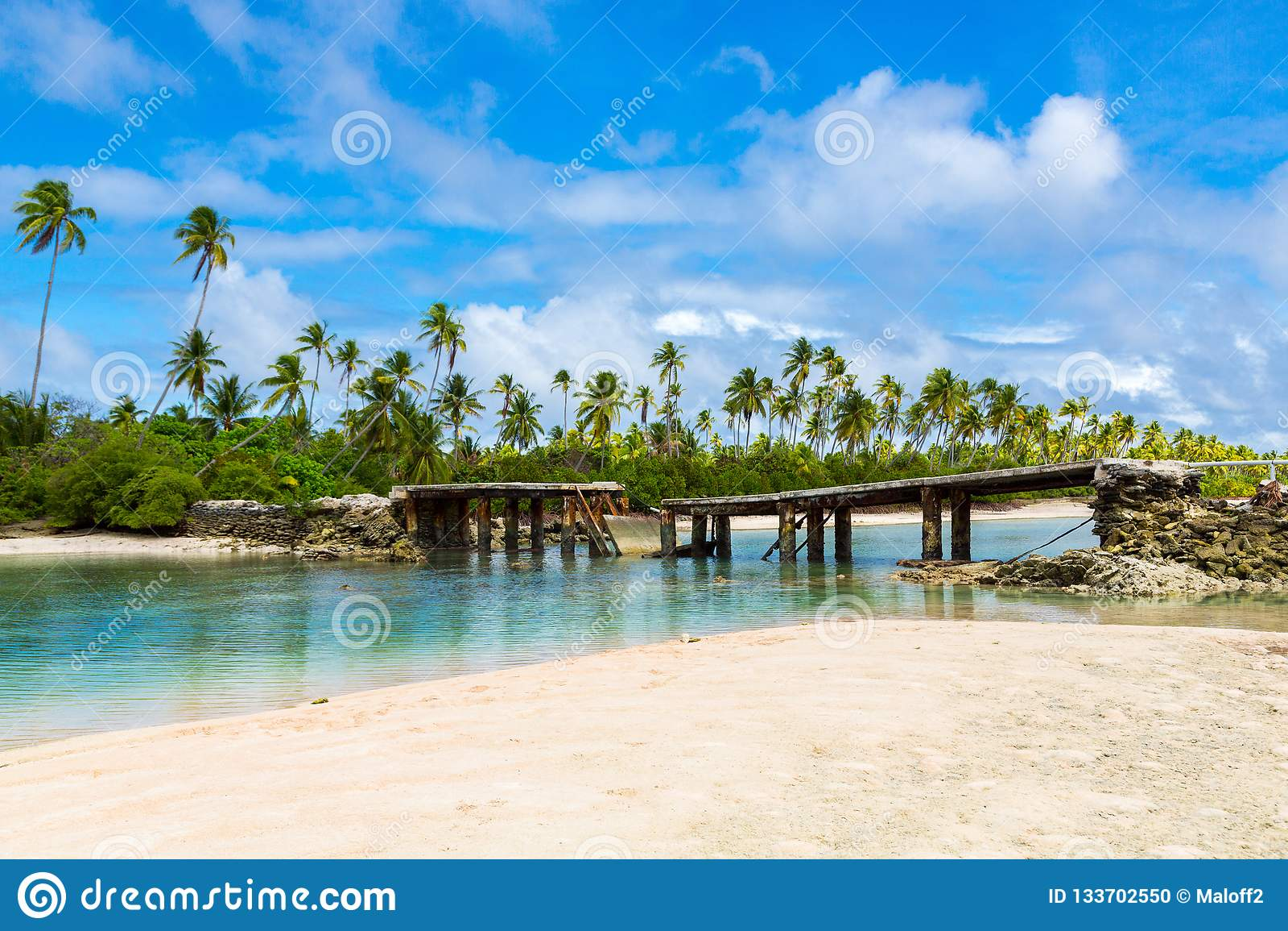 Puente roto debajo de las palmeras entre los islotes sobre la laguna, atolón de Tarawa del norte, Kiribati, Micronesia, islas de