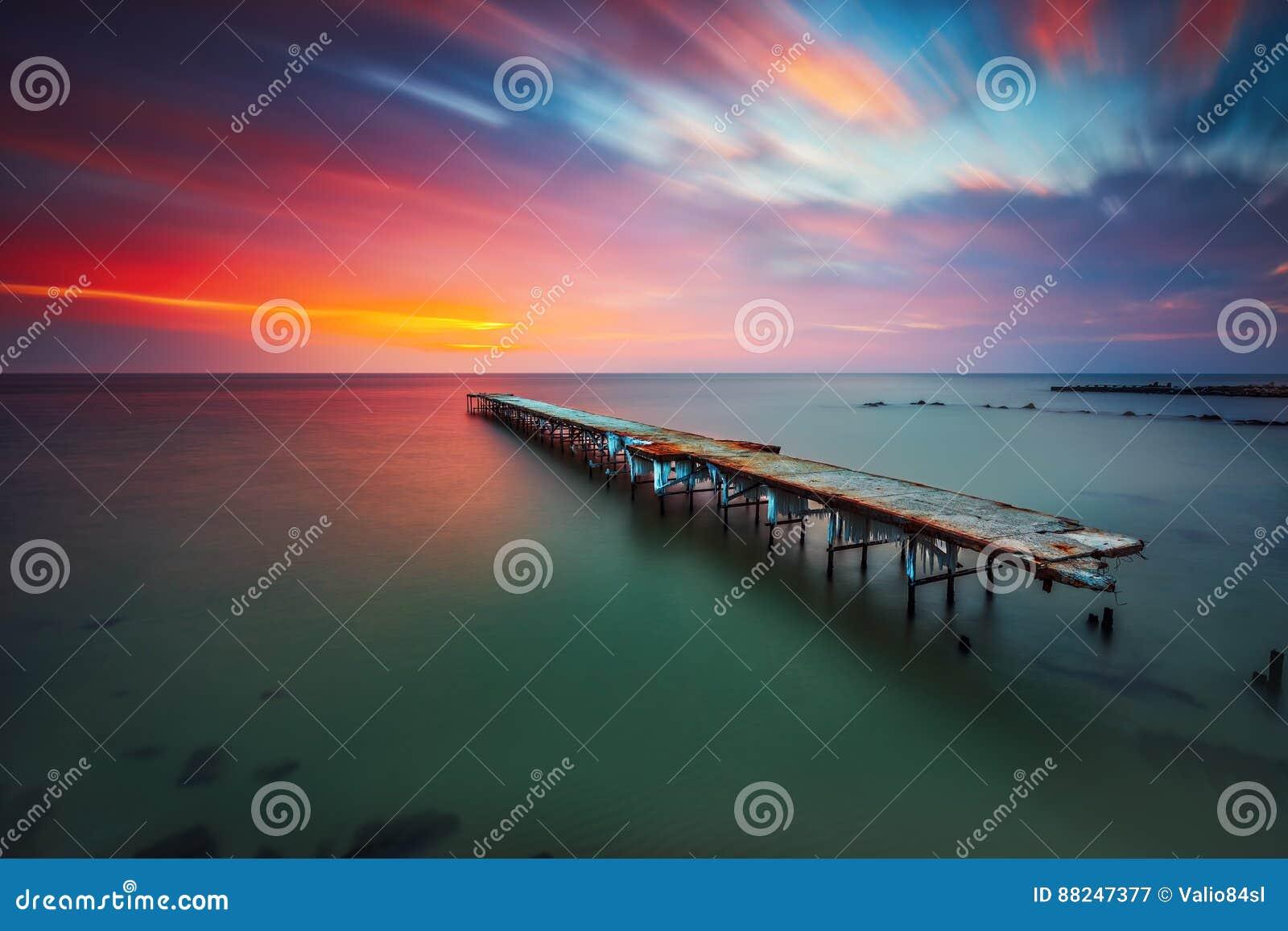 Puente roto viejo en el mar, exposición larga