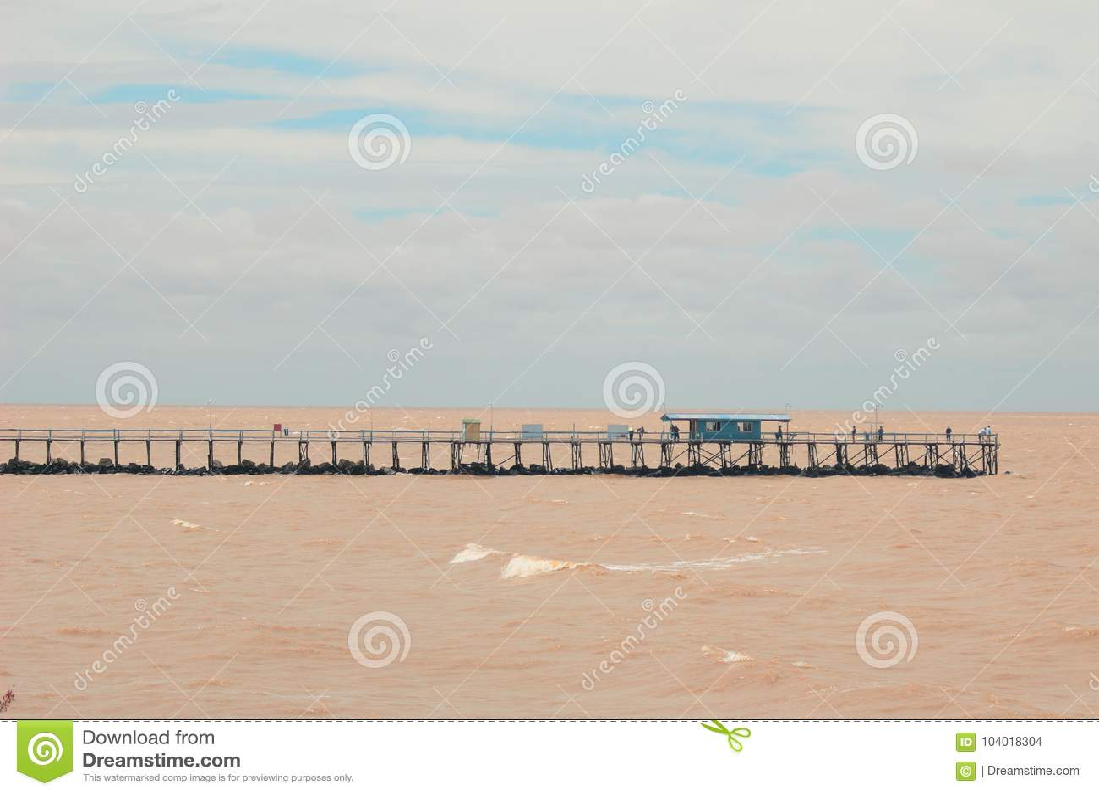 Puente sobre el Brown RÃo de La Plata en la Argentina, Buenos Aires con una pequeña casa azul y un cielo azul