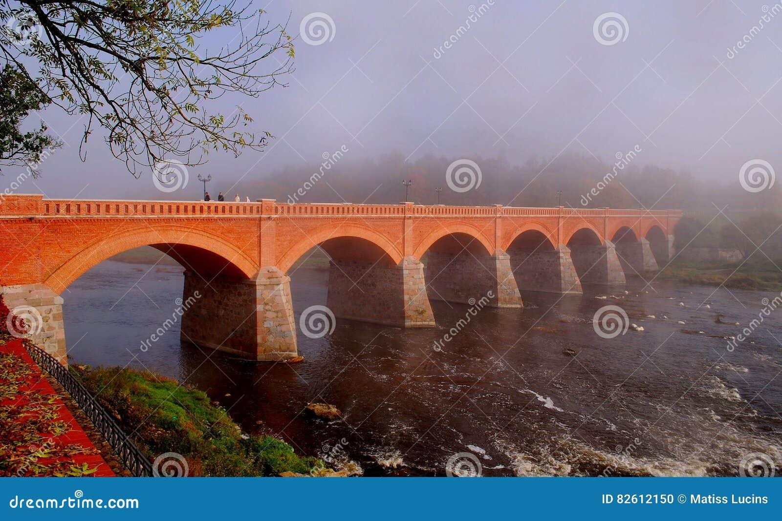 Puente viejo del ladrillo a través del río Venta