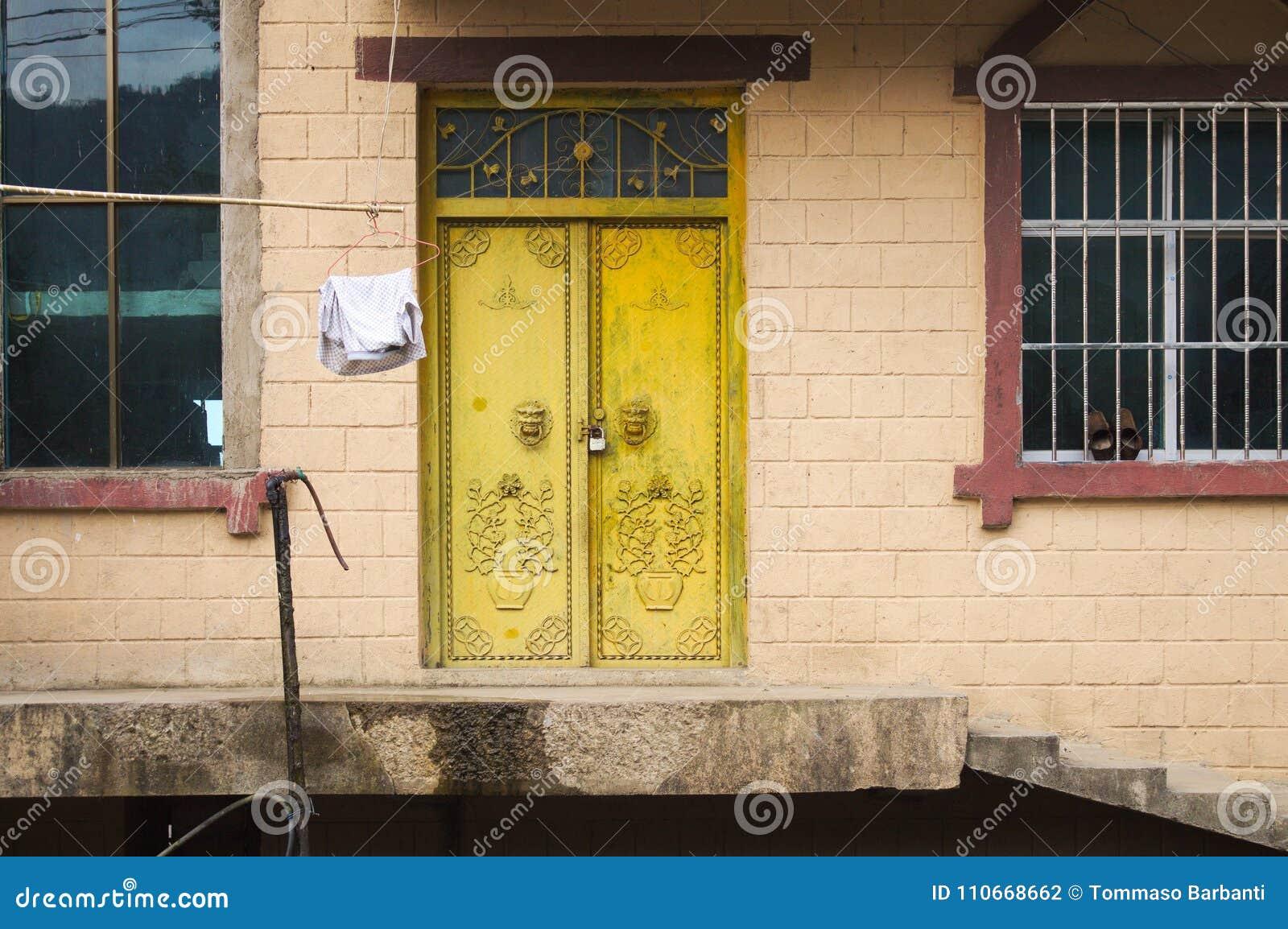Puerta amarilla de una casa rural en Yuanyang