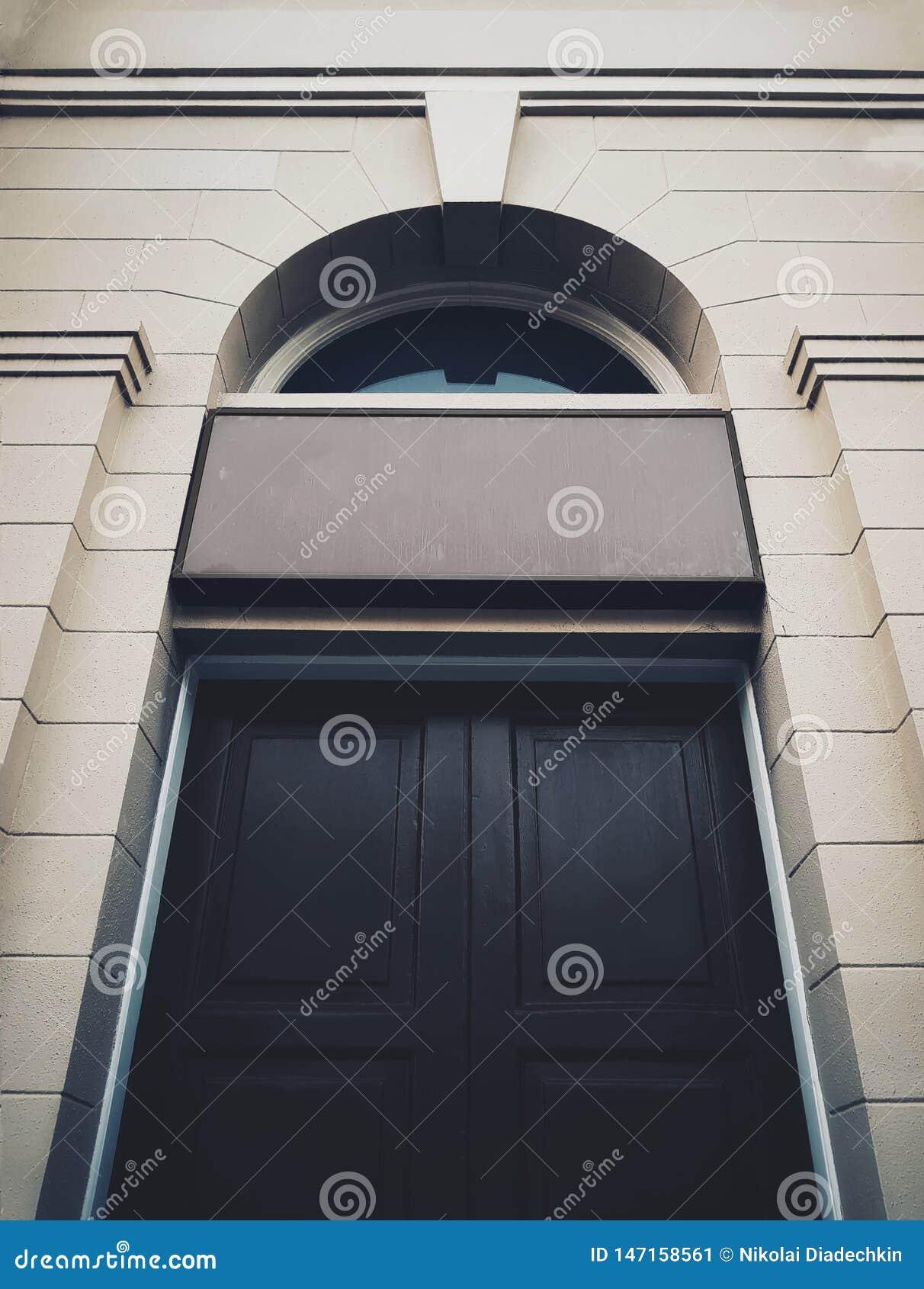 Puerta constructiva histórica negra con singboard de la entrada