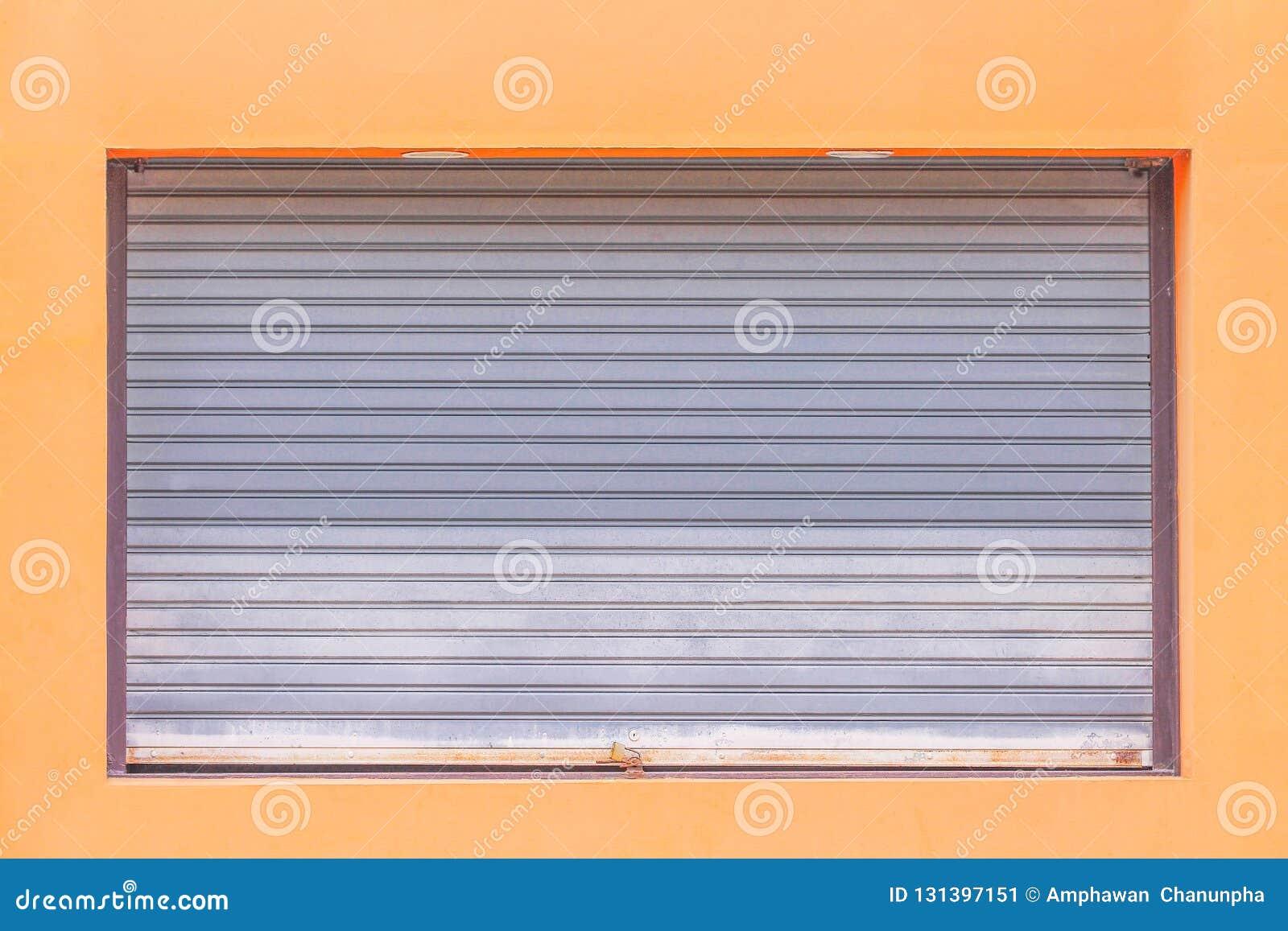 Puerta de acero rodante gris o puerta del obturador del rodillo con el candado en el fondo anaranjado de la pared, modelos del me