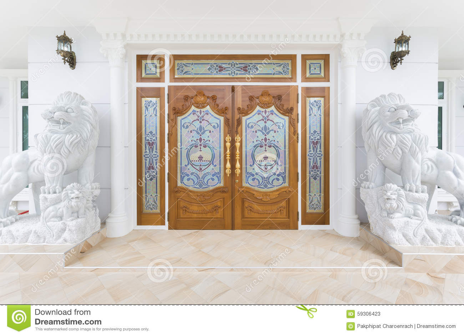 Puerta de madera de la teca con la estatua blanca de los leones