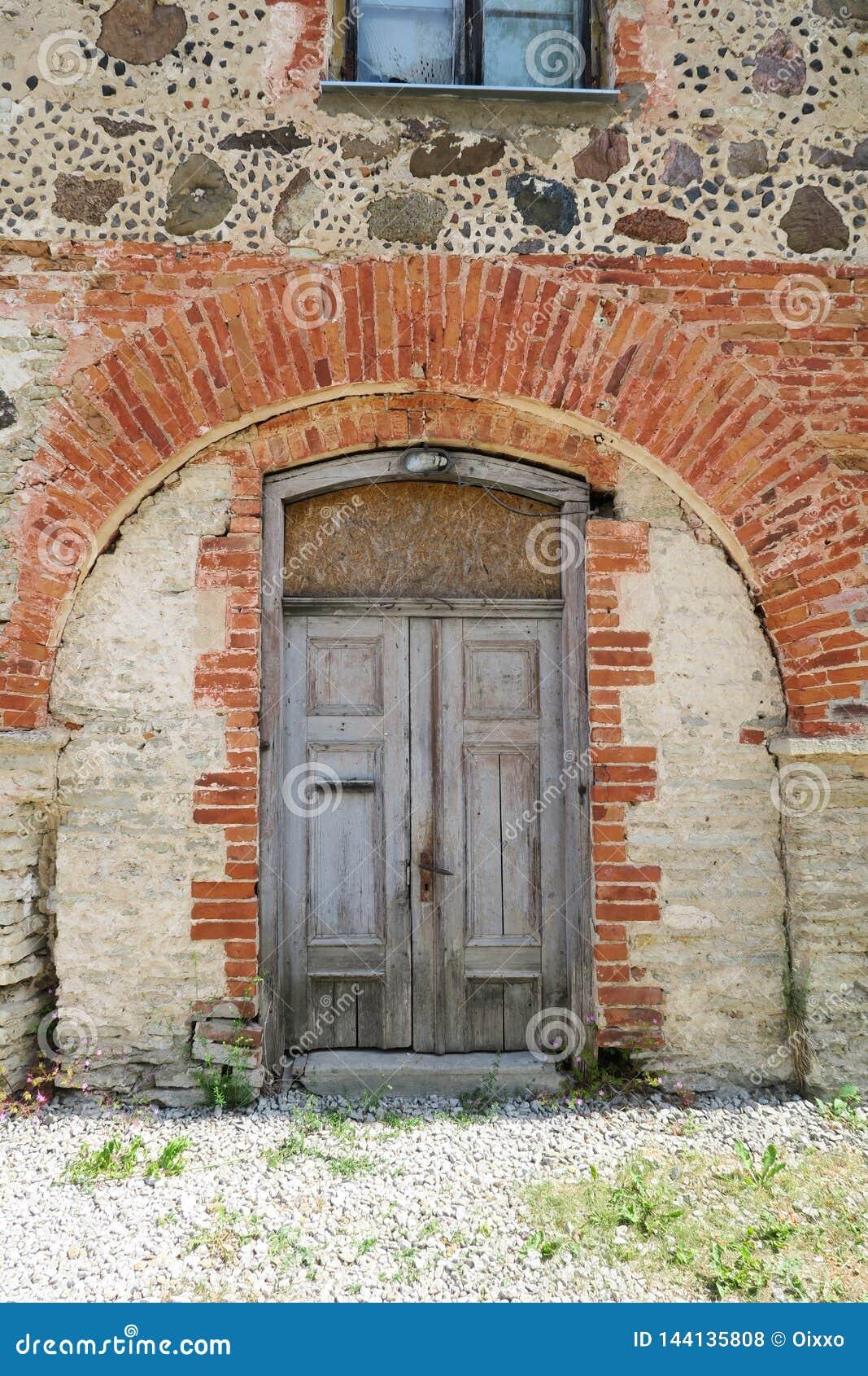Puerta de madera medieval vieja en una pared de piedra