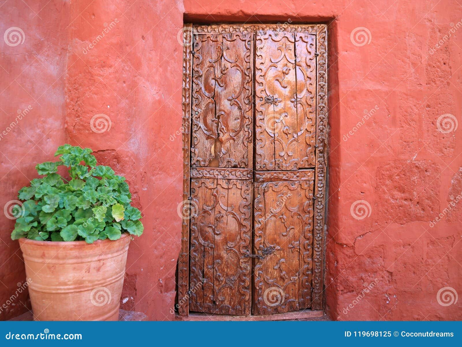 Puerta de madera tallada vieja en la pared áspera anaranjada del color rojo con los plantadores grandes de una terracota en Santa