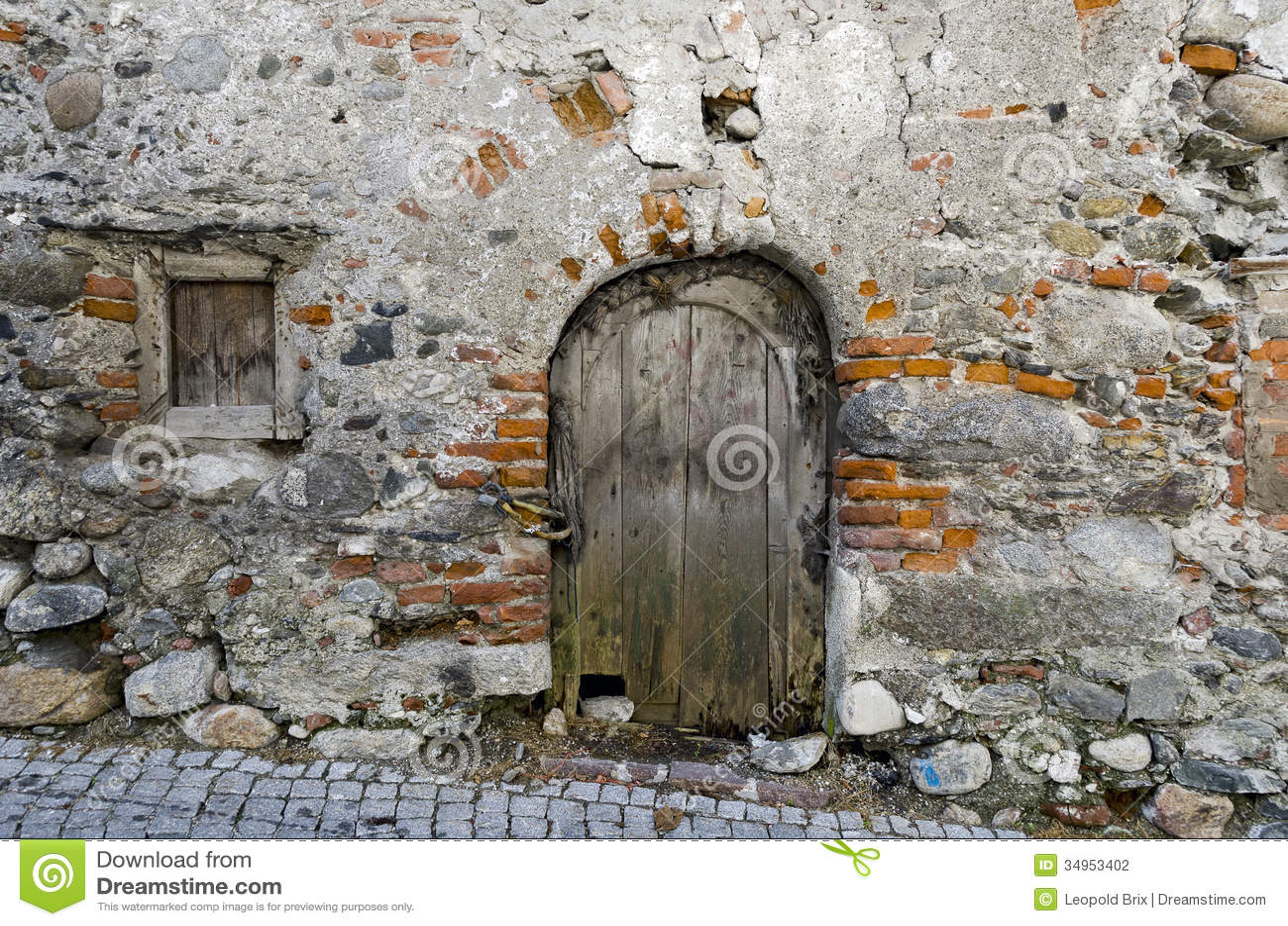 Puerta de madera vieja en una pared solitaria fotograf a for Como barnizar una puerta vieja