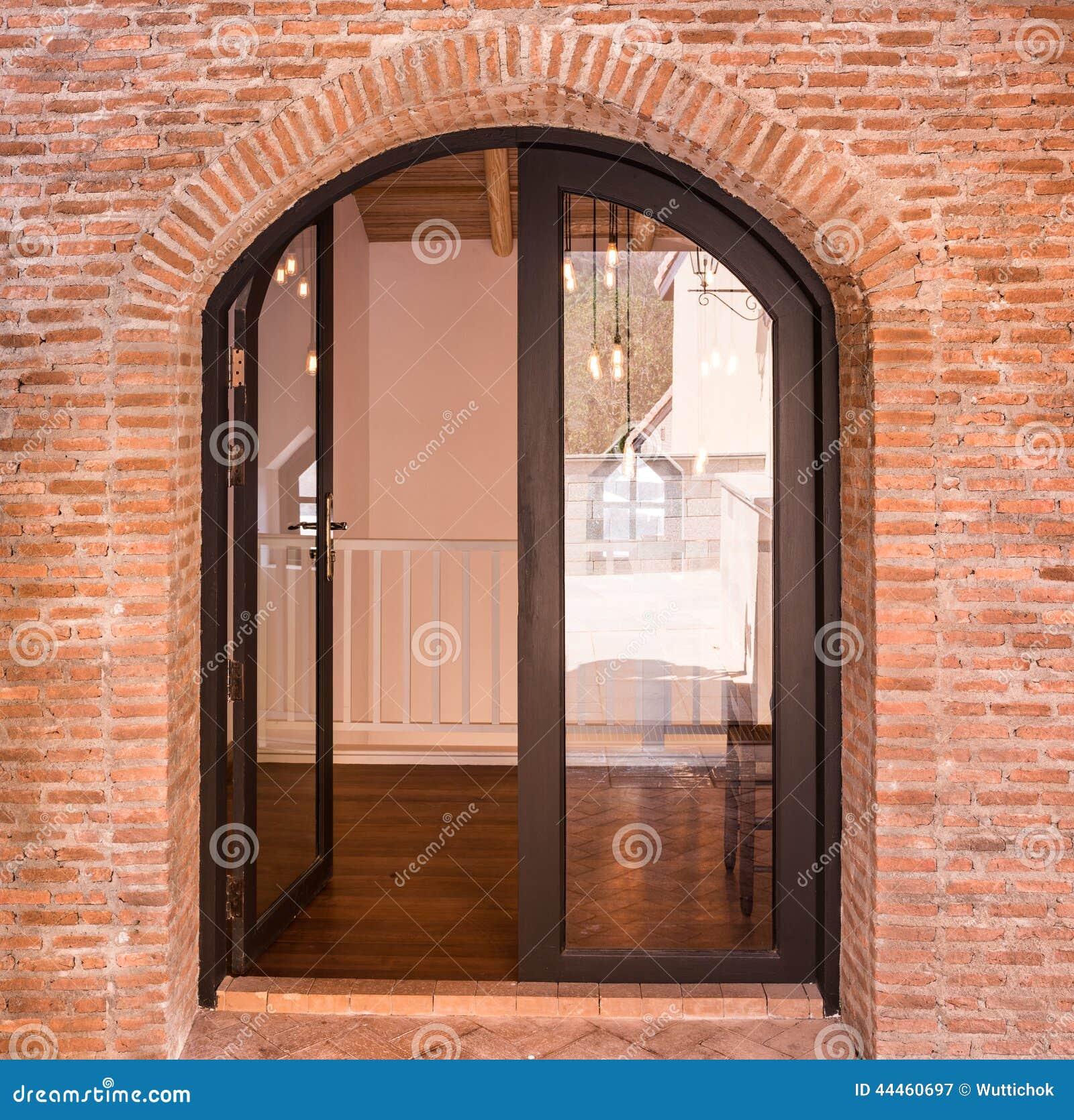 puerta negra del arco en la pared de ladrillo roja foto de