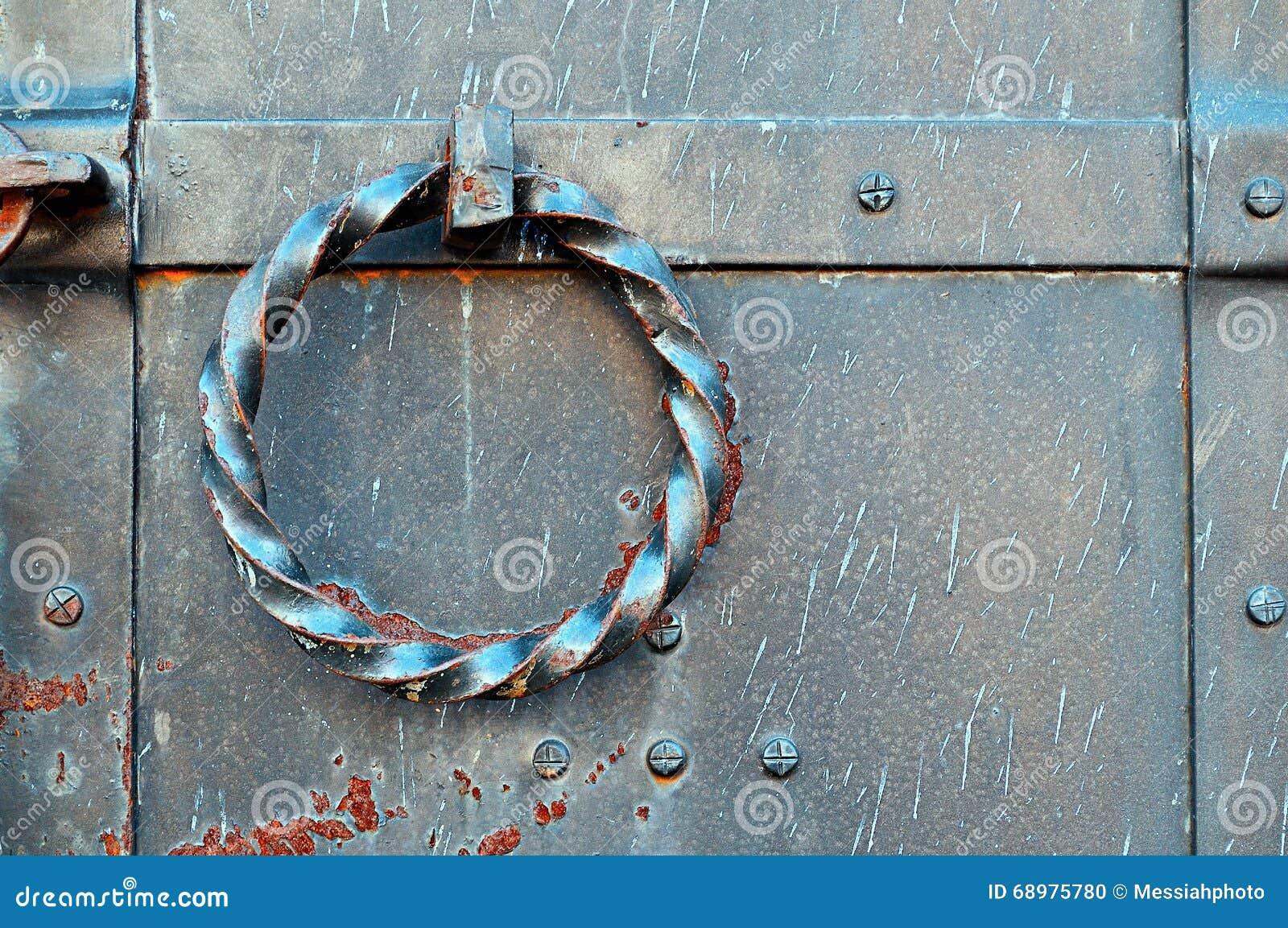 Puerta vieja del metal del grunge con los remaches y el tirador de puerta oxidado torcido bajo la forma de anillo